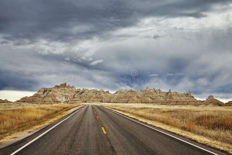 美丽如画的路在有风雨如磐的天空的恶地国家公园 免版税图库摄影
