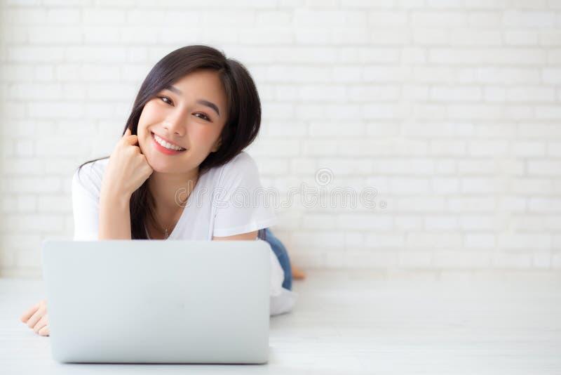 美丽工作网上膝上型计算机的画象亚裔少妇说谎在地板砖水泥背景 库存照片