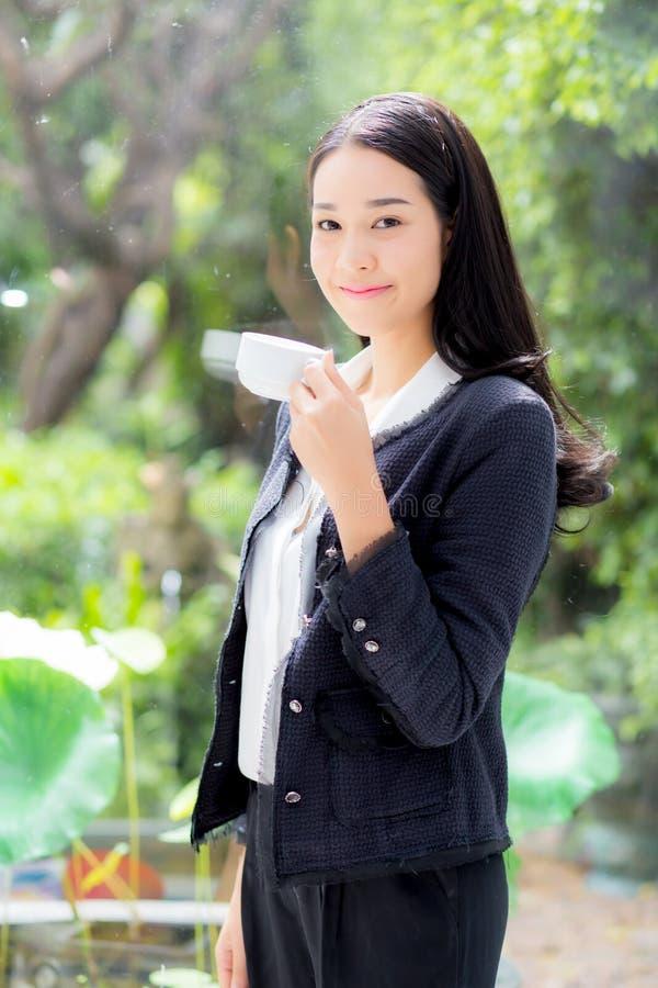美丽有站立的微笑的画象亚裔年轻女实业家拿着饮料coffe 免版税库存图片