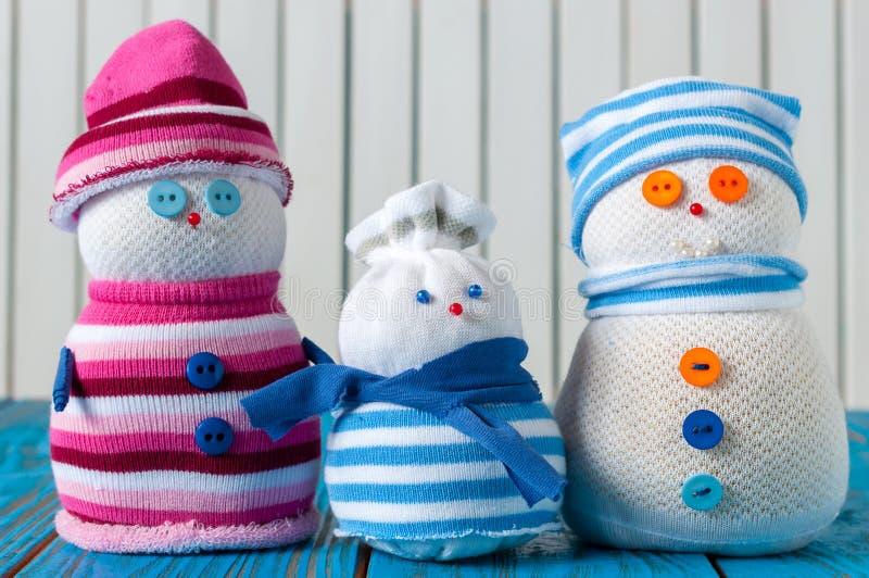 美丽木的愉快的年轻家庭雪人 免版税库存照片