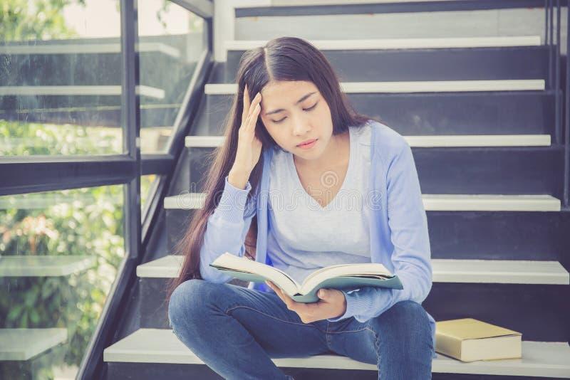 美丽画象亚裔少妇拿着书,女孩疲倦了并且使阅读书学习不耐烦 免版税库存图片