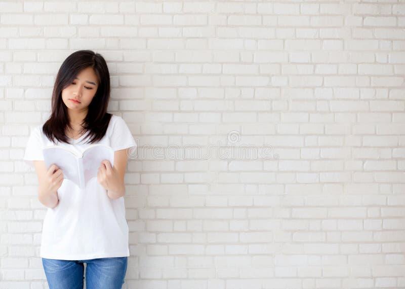 美丽画象年轻亚洲妇女幸福在家放松在具体水泥白色背景的站立的看书 免版税库存照片