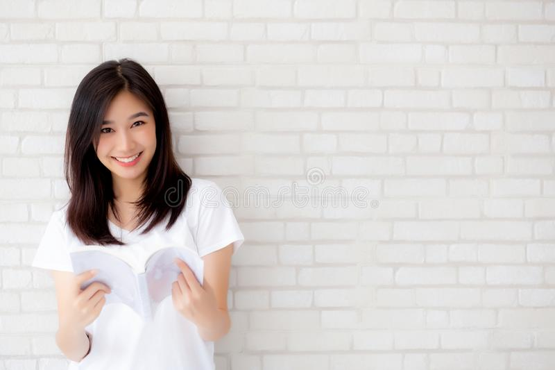 美丽画象年轻亚洲妇女幸福放松在具体水泥白色背景的常设阅读书 库存照片