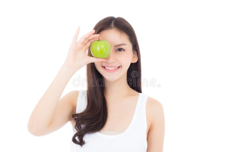 美丽画象年轻亚洲妇女微笑和拿着与心脏形状的绿色苹果果子 免版税图库摄影