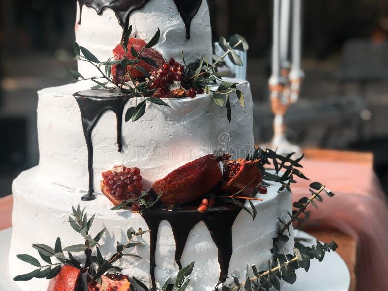 美丽的三层白色奶油婚宴喜饼用石榴果子和鲜花 图库摄影