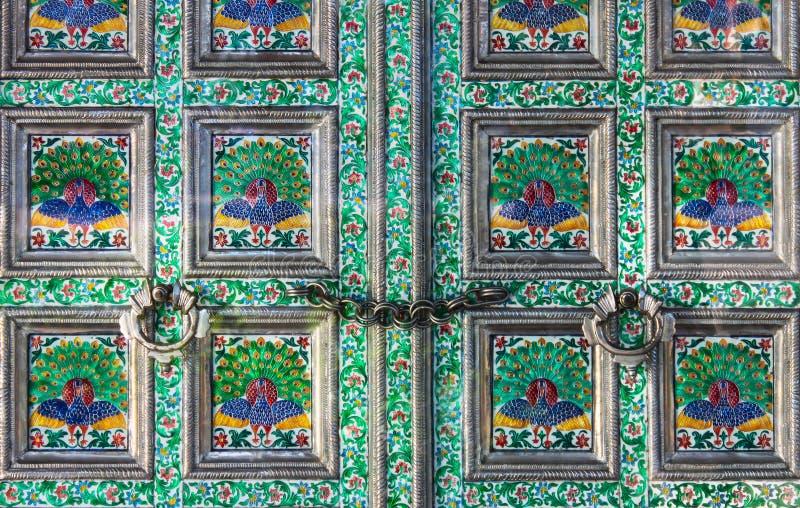 美丽的上釉的门特写镜头与花和孔雀的在框架锁了紧紧与链子 免版税库存图片