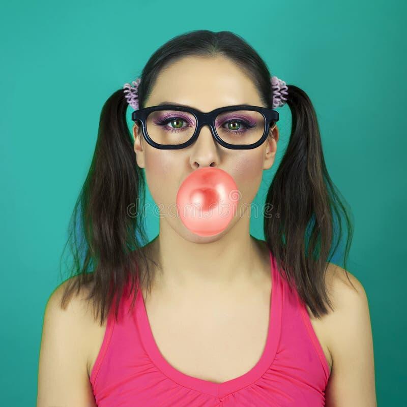 美丽的与口香糖泡影的女孩佩带的行家玻璃  免版税库存照片