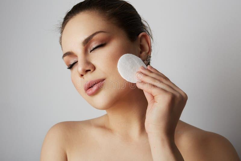 美丽的与白色化装棉的女孩刷新的皮肤面孔在灰色演播室背景 与轻的裸体构成的模型 库存图片