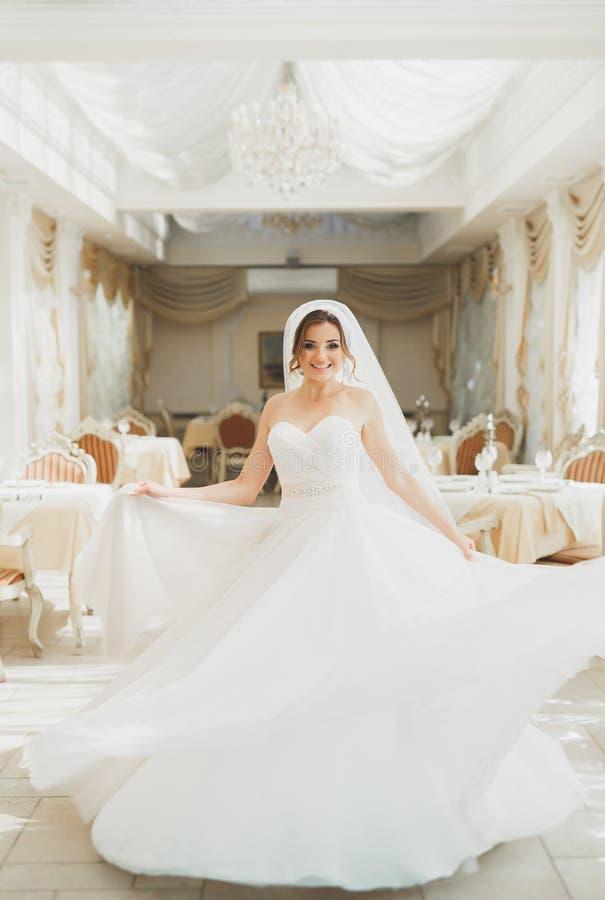 美丽的与羽毛的新娘佩带的时尚婚礼礼服与豪华欢欣构成和发型,室内演播室 图库摄影