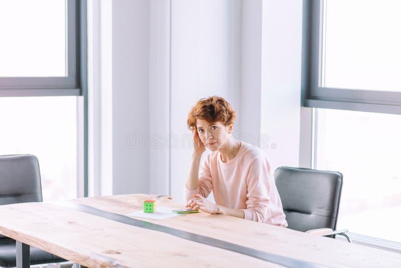 美丽的严肃的女孩坐与电话在办公室屋子 免版税库存图片
