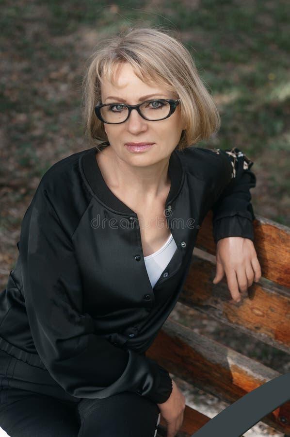 美丽的中年妇女坐公园长椅 特写镜头酸碱度 免版税图库摄影