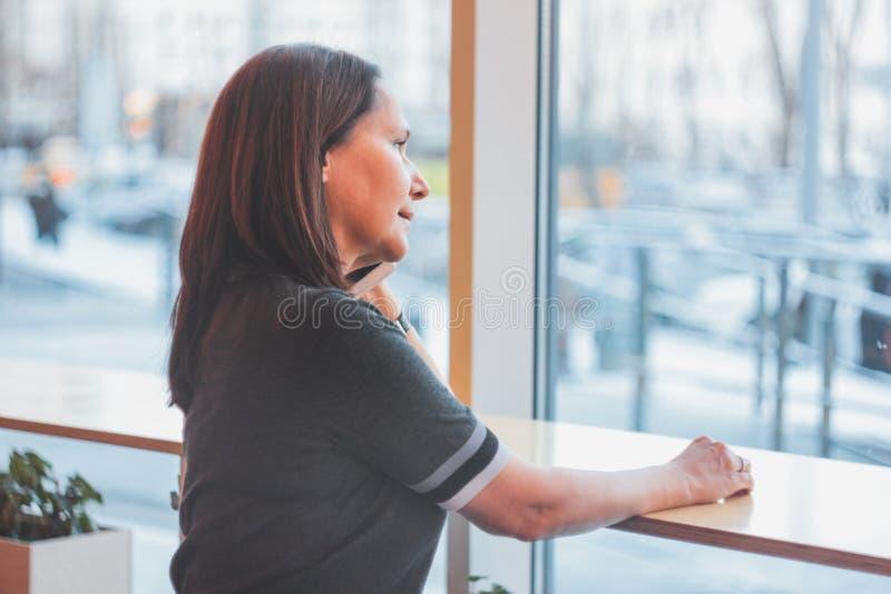 美丽的中年妇女微笑和谈话在pho 免版税库存照片