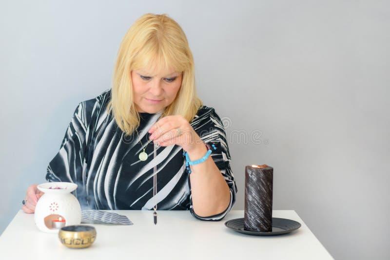 美丽的中年妇女画象在有占卜用的纸牌、黑摆锤和蜡烛的一张算命先生一定书桌附近坐 免版税库存图片