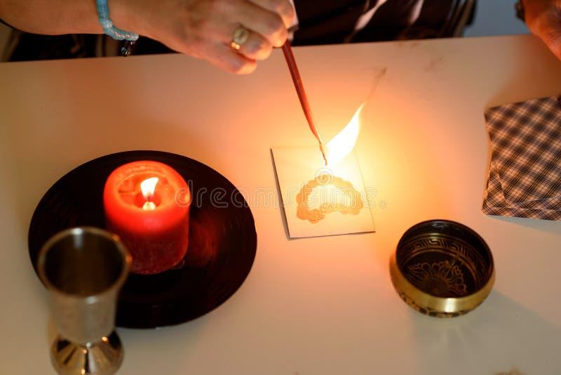 美丽的中年妇女画象在有占卜用的纸牌、黑摆锤和蜡烛的一张算命先生一定书桌附近坐 免版税库存照片