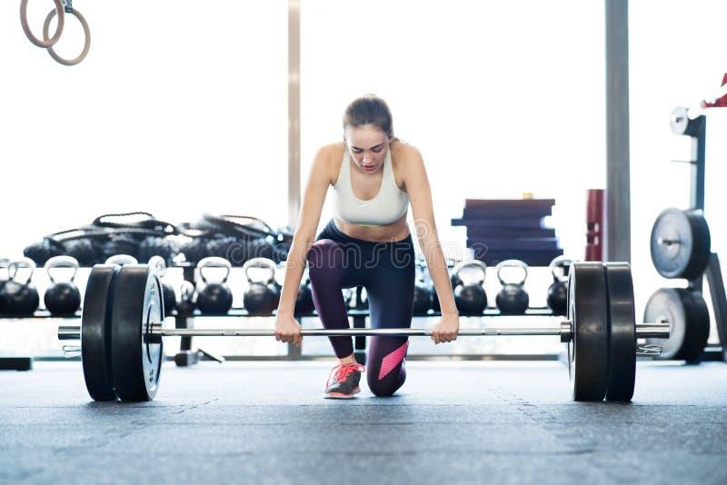 美丽的举重的杠铃的健身房的年轻人适合的妇女 库存图片