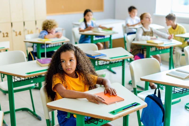 美丽的乏味非裔美国人的女小学生坐与同学的教训被弄脏 免版税库存照片