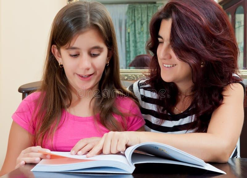 美丽的书女孩她的母亲读取 库存照片