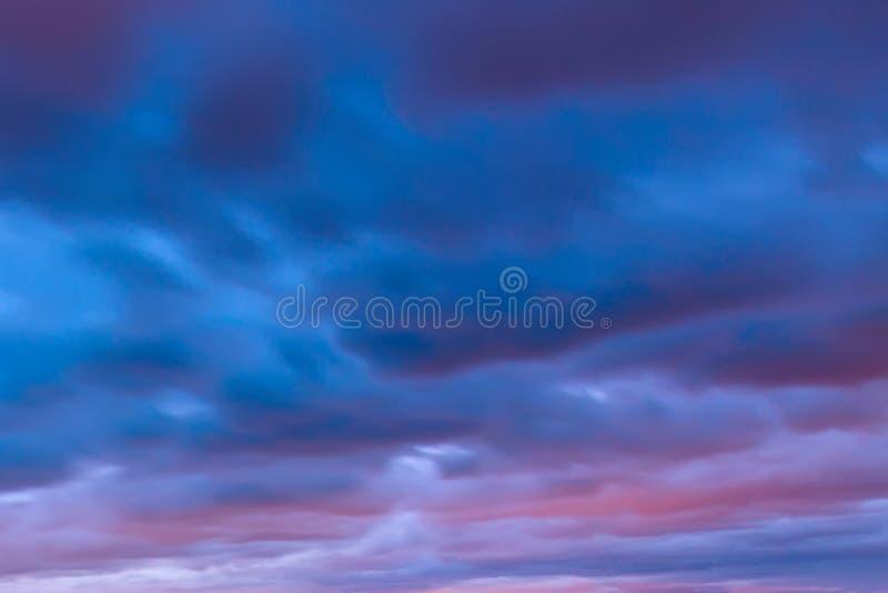 美丽的五颜六色的天空背景  r 剧烈的桃红色,紫色和蓝色多云日落天空 r 库存照片