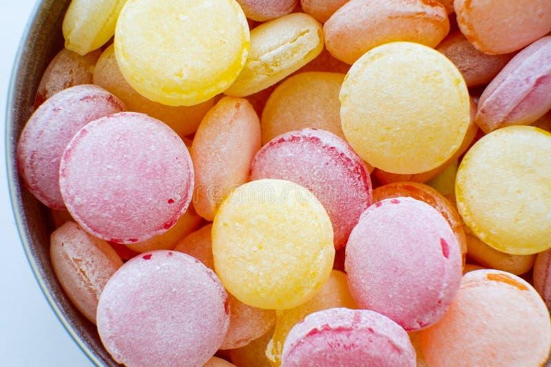 美丽的五颜六色的棒棒糖特写镜头 在罐子箱子的巧克力坚果 黄色,橙色,红色,紫色,桃红色,明亮的糖果 库存图片
