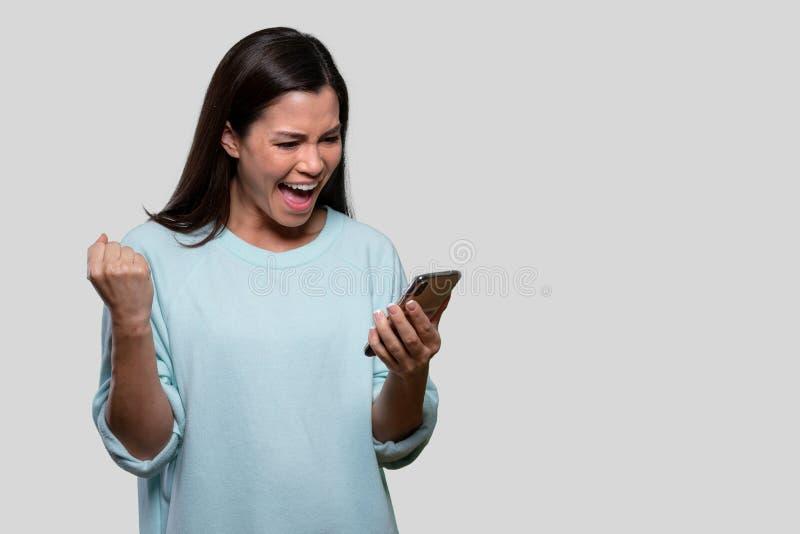 美丽的亚洲女人兴奋和幸福,手拿手机庆祝成功,好消息,广告 免版税库存图片