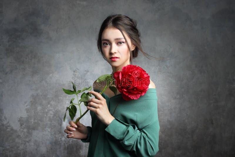 美丽的亚洲妇女举行牡丹花 化妆用品,构成 香料厂概念 库存图片