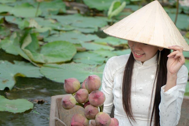 美丽的亚洲妇女戴白色传统越南礼服Ao Wai和越南农夫的帽子和坐在流程的木小船 免版税库存图片