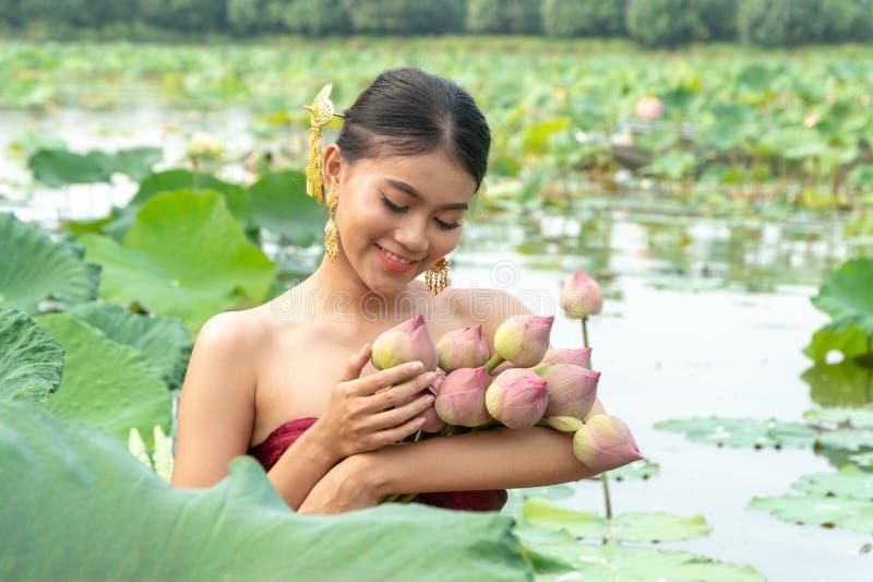 美丽的亚洲妇女穿传统泰国礼服和坐木小船在花莲花湖 她的手举行桃红色 图库摄影