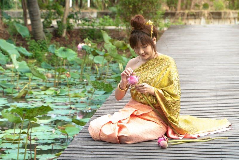 美丽的亚洲妇女穿传统泰国礼服和坐木桥 她的手在尊敬手里在泰国 库存图片