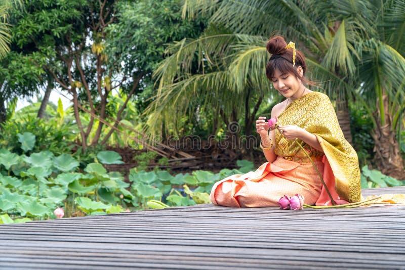 美丽的亚洲妇女穿传统泰国礼服和坐木桥 她的手在泰国猪圈的尊敬手里 免版税库存图片