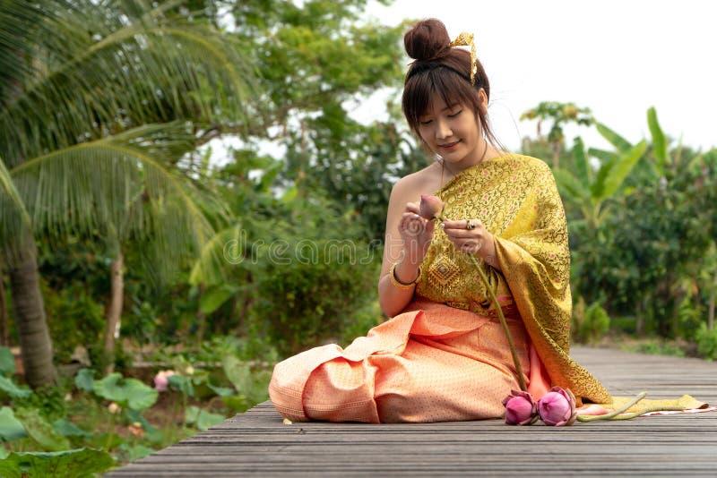 美丽的亚洲妇女穿传统泰国礼服和坐木桥 她的手在thailandBeau的尊敬手里 免版税库存照片