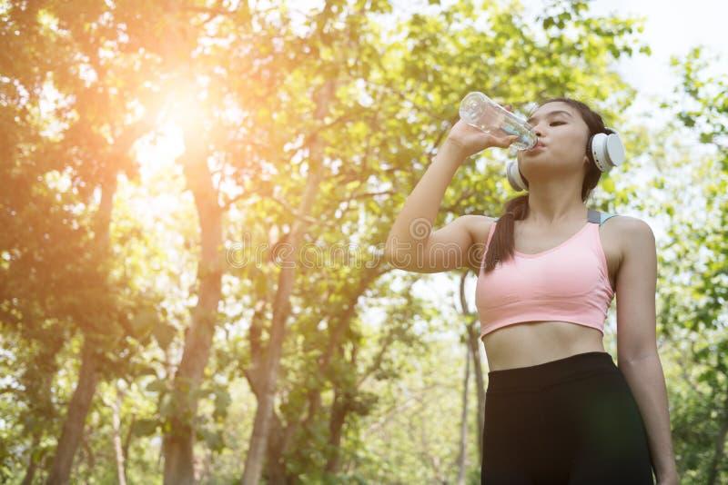 年轻美丽的亚裔健身运动员妇女饮用水以后 库存图片