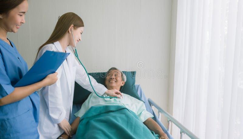 美丽的亚裔医生在医院病床上听心脏病人 图库摄影