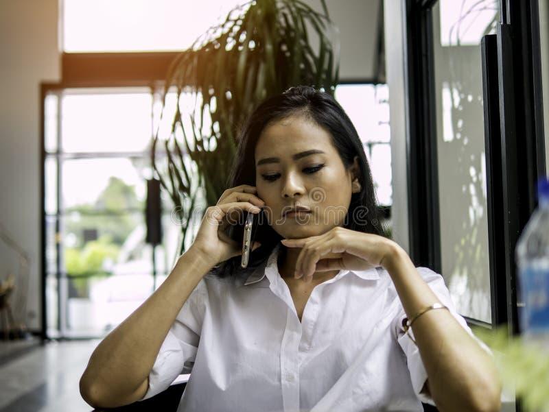 美丽的亚裔听女商人拿着智能手机的手中和严重的集中与忧虑的一个电话 免版税库存照片