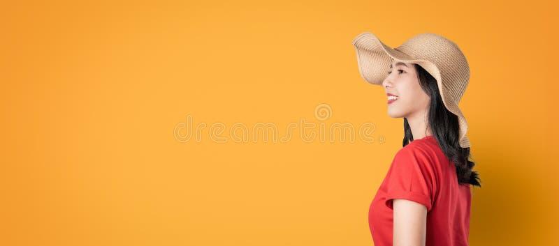 美丽的亚裔在橙色背景的妇女好皮肤身分今后面对和愉快地看和微笑 免版税图库摄影
