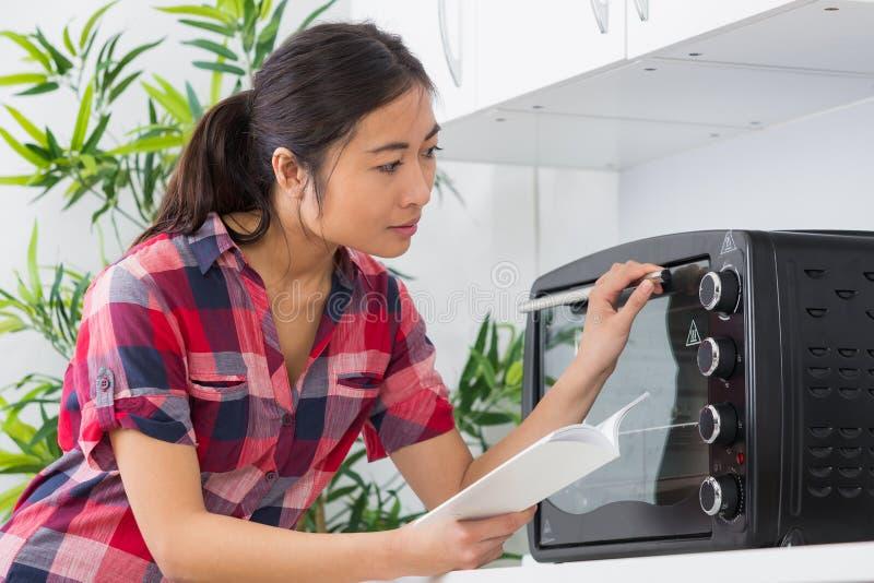美丽的亚裔在烤箱的妇女移动的定时器瘤 免版税库存图片