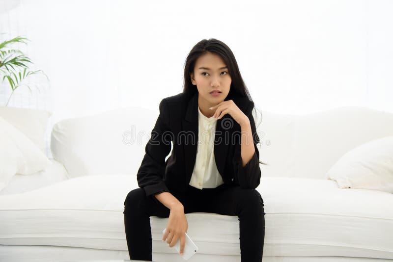 美丽的亚裔女商人坐白色沙发 图库摄影
