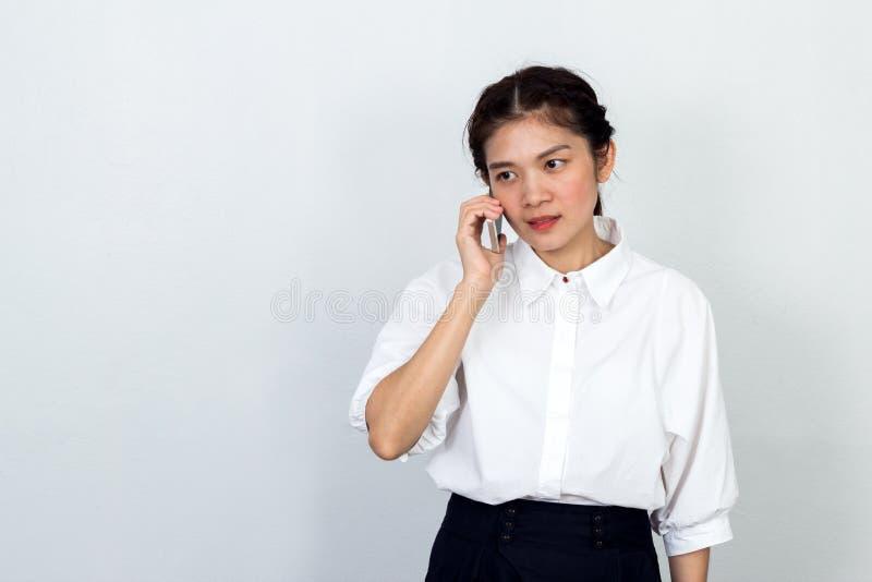 美丽的亚裔女商人谈话在白色的手机 库存图片