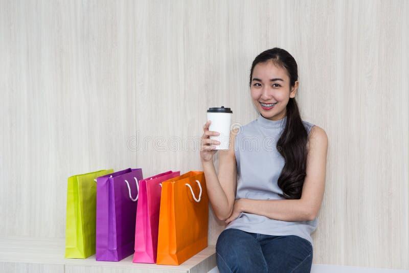 美丽的亚裔女孩、年轻顾客、五颜六色的纸袋和咖啡杯 库存图片