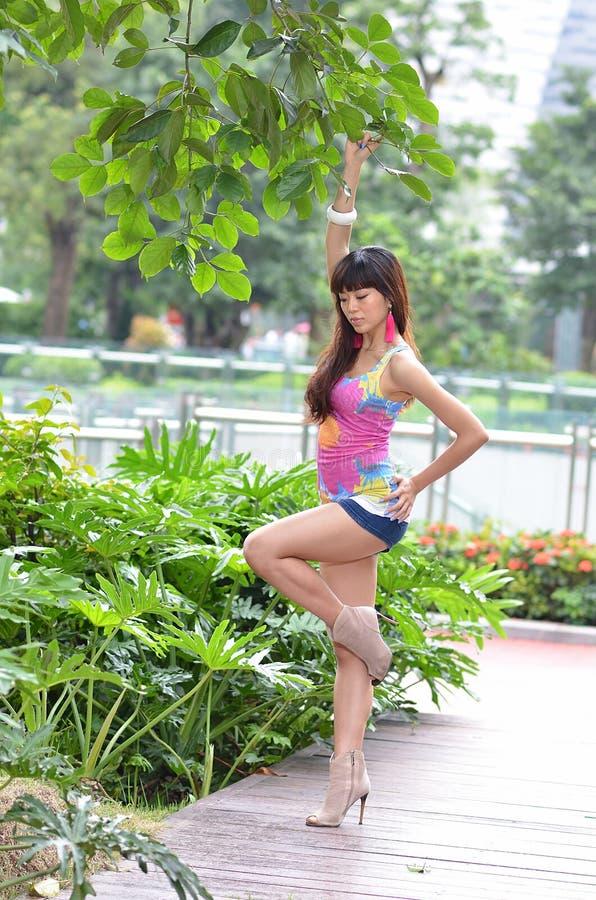 美丽的亚裔女孩在公园显示她的青年时期 库存图片
