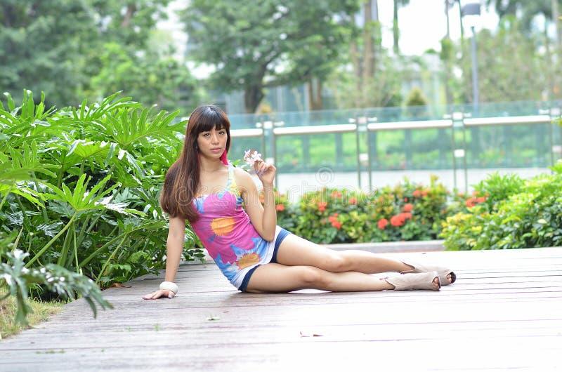 美丽的亚裔女孩在公园显示她的青年时期 免版税图库摄影