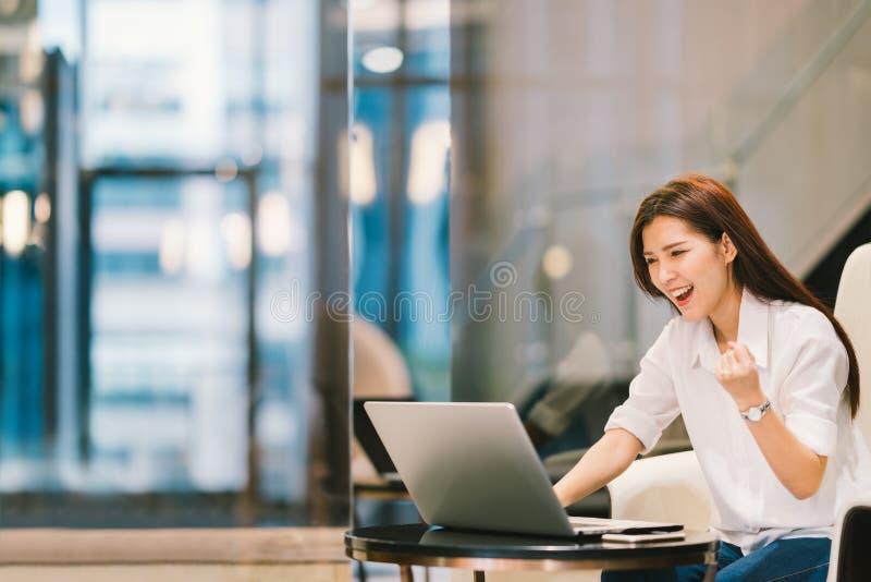 美丽的亚裔女孩庆祝与膝上型计算机、成功姿势、教育或者技术或者起动企业概念,与拷贝空间 免版税库存照片