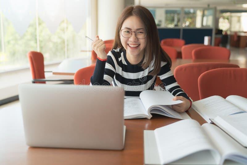 美丽的亚裔女孩庆祝与膝上型计算机、成功或者愉快的姿势、教育或者技术或者起动企业概念 免版税库存照片