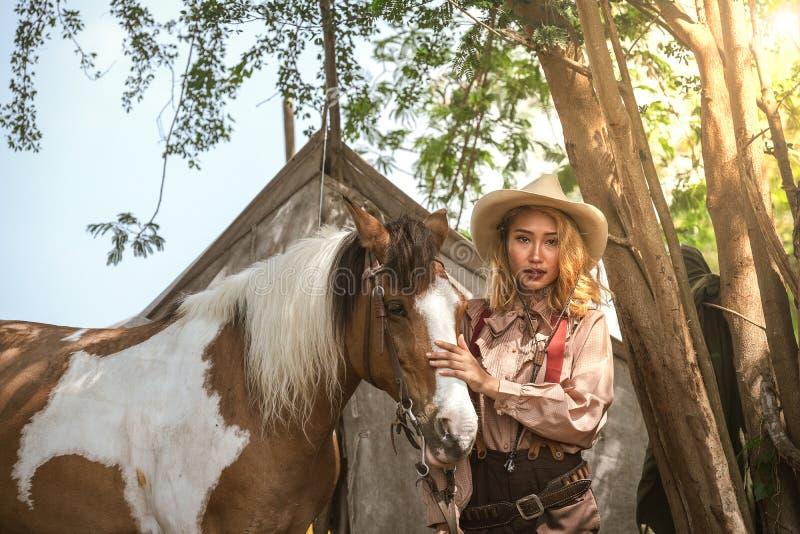 美丽的亚裔女孩牛仔照顾她的与爱关心的马 免版税库存照片
