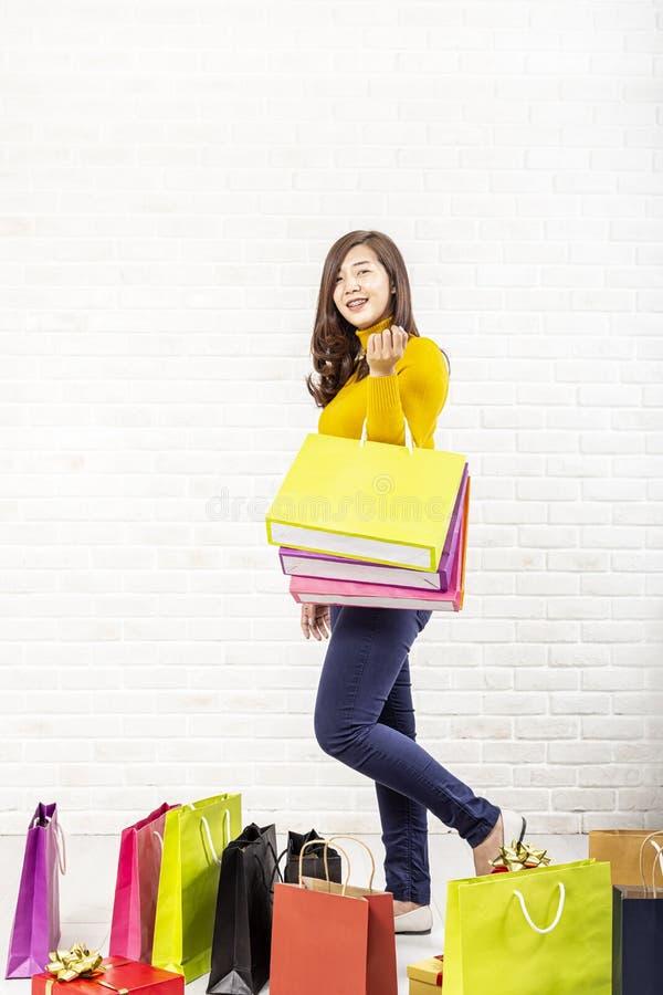 美丽的亚裔女孩运载的购物带来 购物的妇女微笑 美丽的亚裔女孩 砖背景的年轻顾客 库存图片