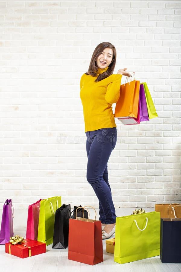 美丽的亚裔女孩运载的购物带来 购物的妇女微笑 美丽的亚裔女孩 砖背景的年轻顾客 库存照片