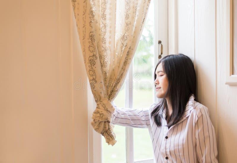美丽的亚裔女性画象放松,并且在家站立在窗口附近,正面认为,好态度,闭上您的眼睛 免版税库存照片