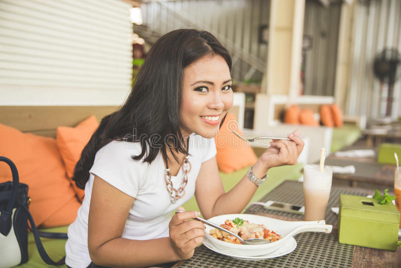 年轻美丽的亚裔妇女在餐馆,享用她的食物 免版税库存图片
