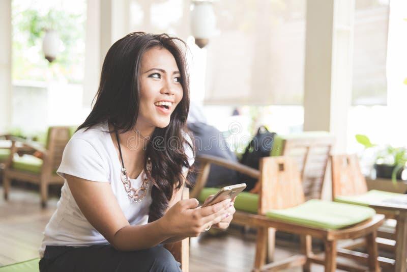 年轻美丽的亚裔妇女在餐馆,拿着手机 免版税库存照片