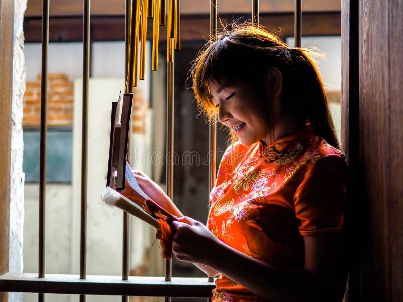 美丽的亚裔妇女在Cheongsam礼服,红色中国礼服 她在有中国内部的入口前面站立 免版税库存图片