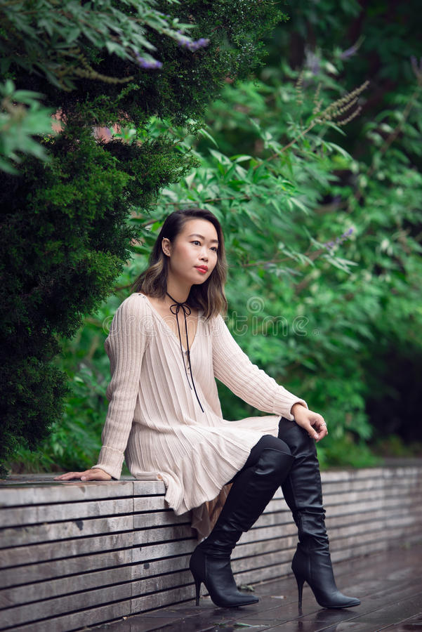 美丽的亚裔妇女坐长凳在绿色公园和单独和认为 免版税库存图片